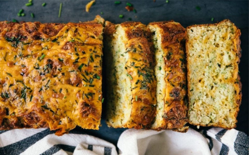 Three slices of cheesy zucchini bread with melted cheddar cheese on top.