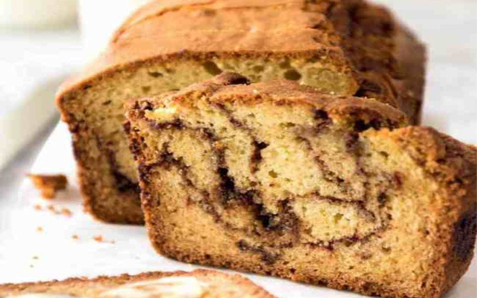 A loaf of Cinnamon Swirl Bread with one slice ready to eat.