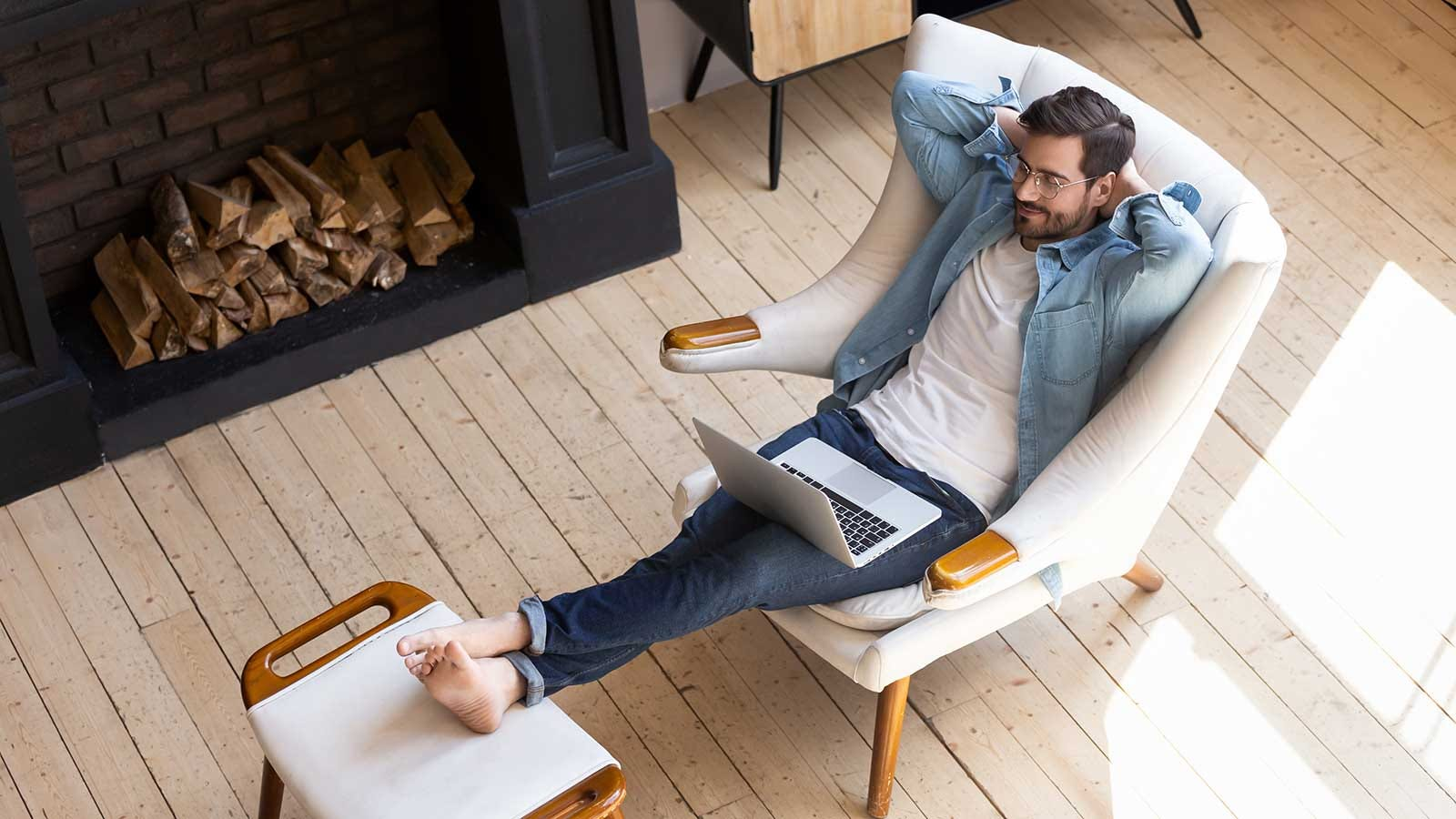 A man relaxing in a chair with his feet up and a laptop on his lap.
