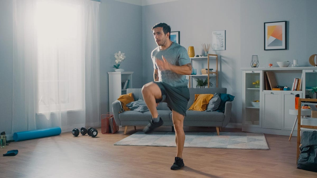 Man doing a high impact workout in his apartment.