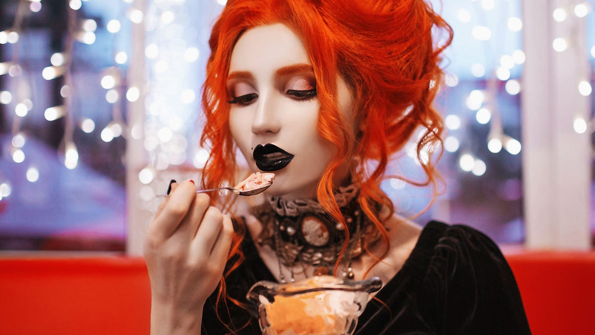 A woman wearing goth-style makeup and clothes and eating a Halloween-themed desert.