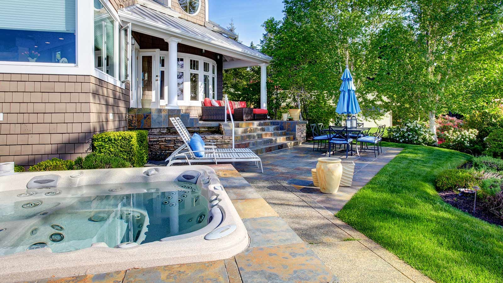 A beautiful home with outdoor furniture, nice landscaping, and a hot tub.