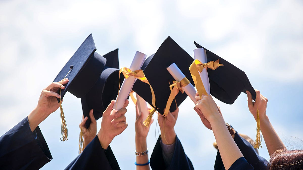 Graduates holding up their caps and diplomas.