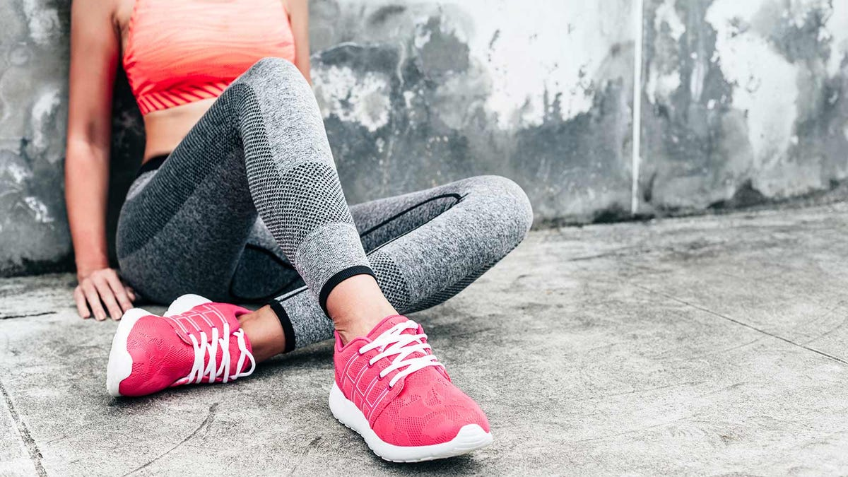 Woman sitting, leaning against a wall, in workout wear taking a break after running.