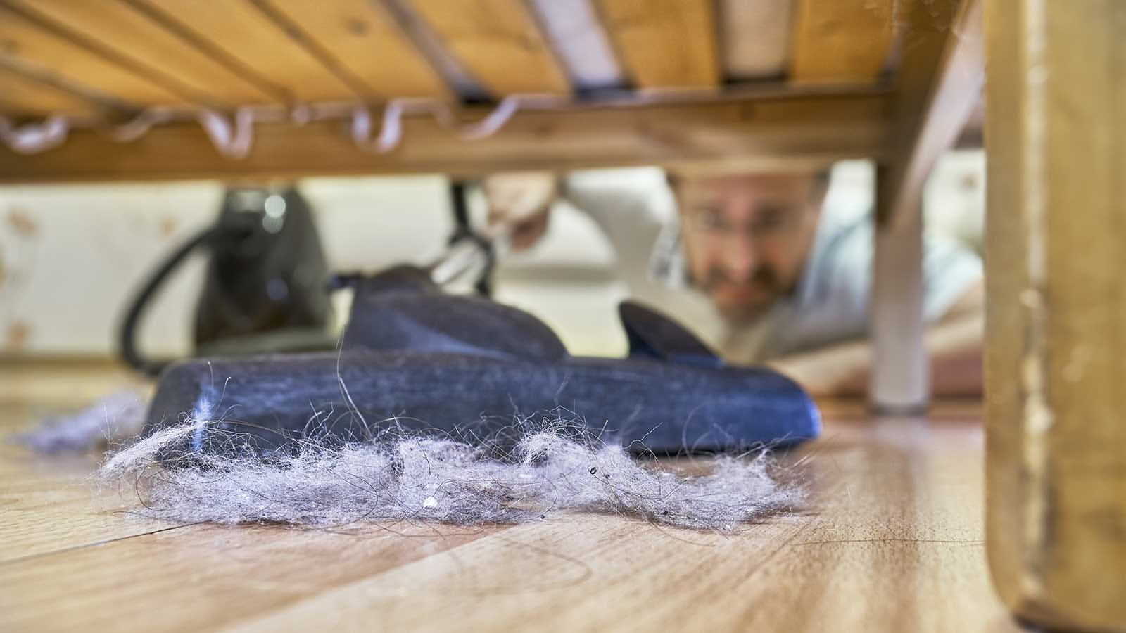 Man vacuuming huge dust bunnies from under his bed.