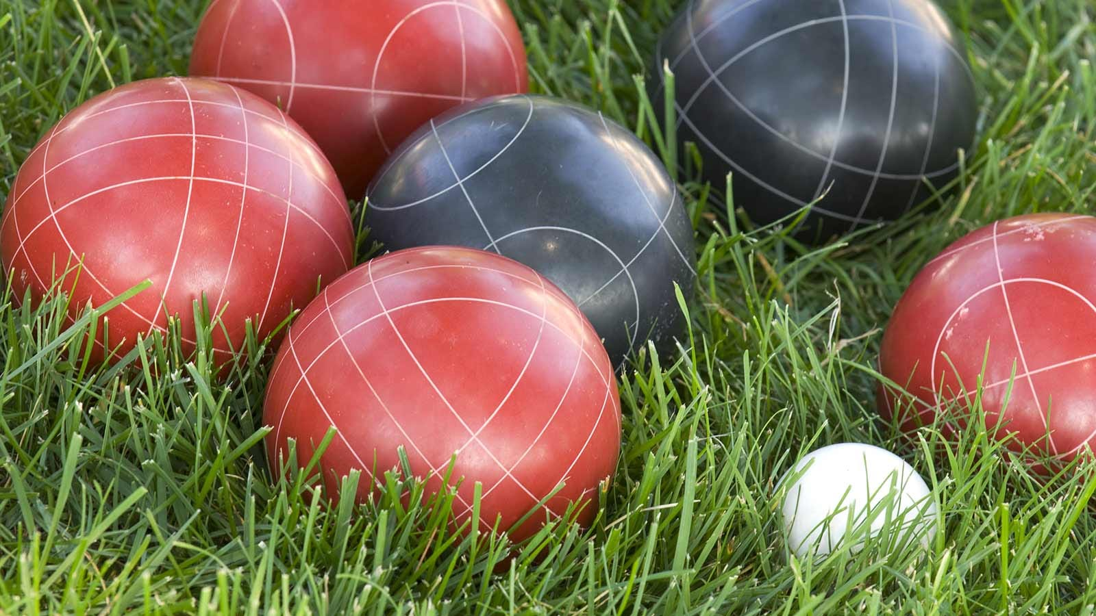 Bocce balls resting on green grass.