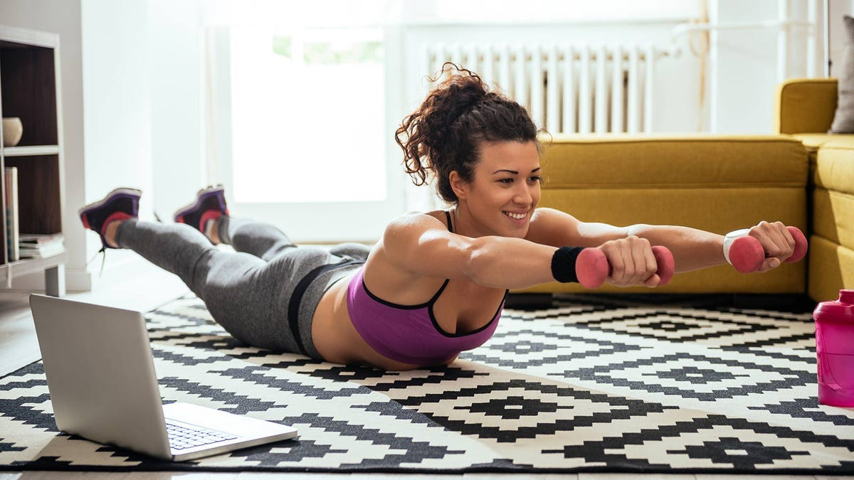 Woman exercising in her living room using remote instruction via her laptop.