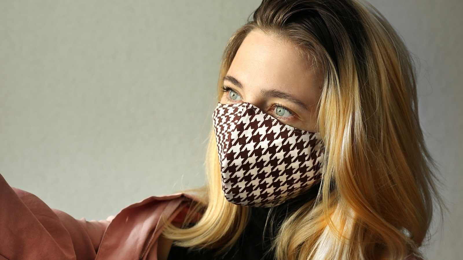A woman wearing a snug-fitting cloth mask.