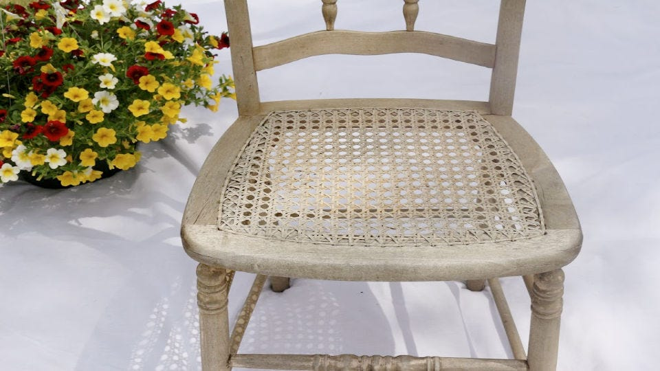 An old chair with a webbed center, next to a planter full flowers.