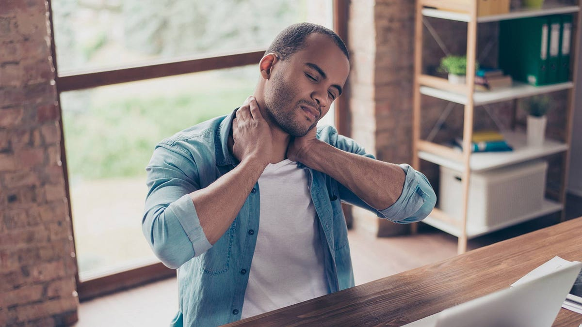 Man rubbing his neck after spending all day at his desk.