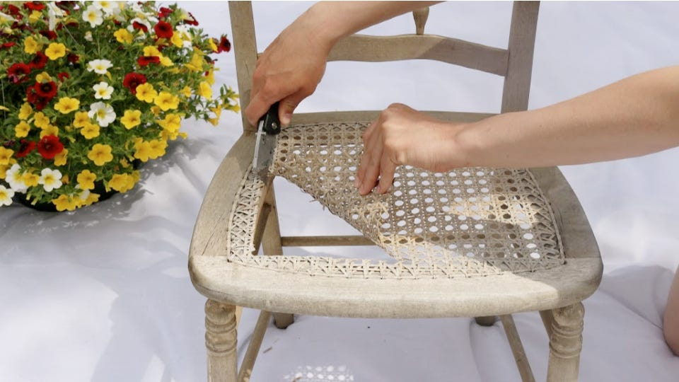 Someone using a utility knife to cut out the center of a chair.