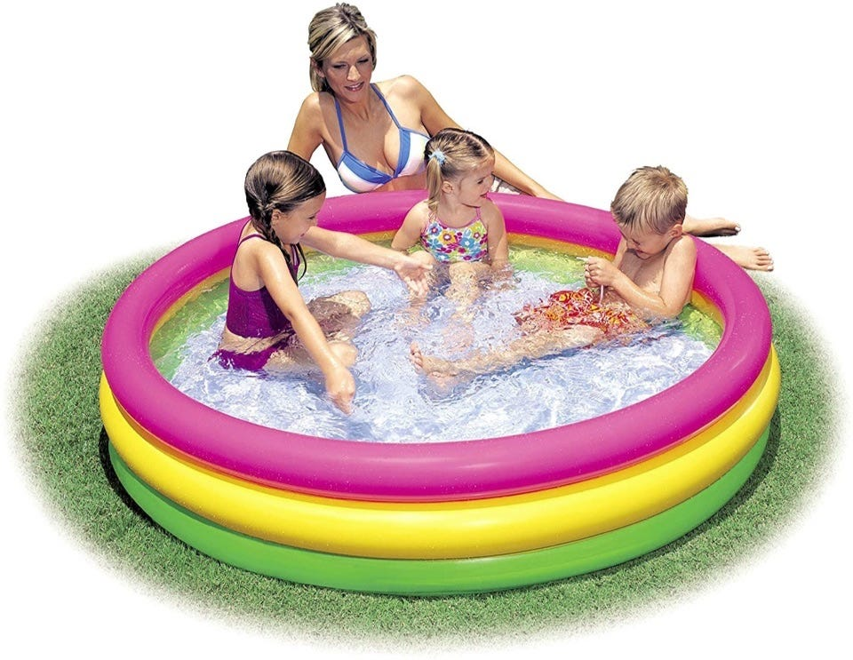 Kids playing in a three ring pool with pink, yellow, and green rings, plus a woman supervising them outside of the pool