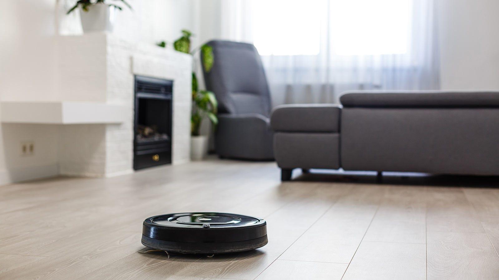 A robotic vacuum cleaner on a hardwood floor.