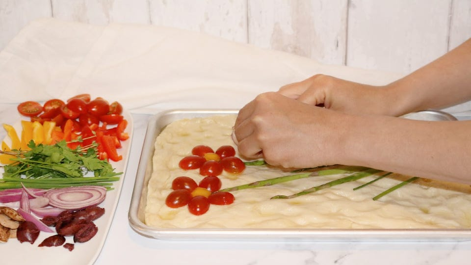 Hands placing various herbs and vegetables on bread dough in the shape of flowers.