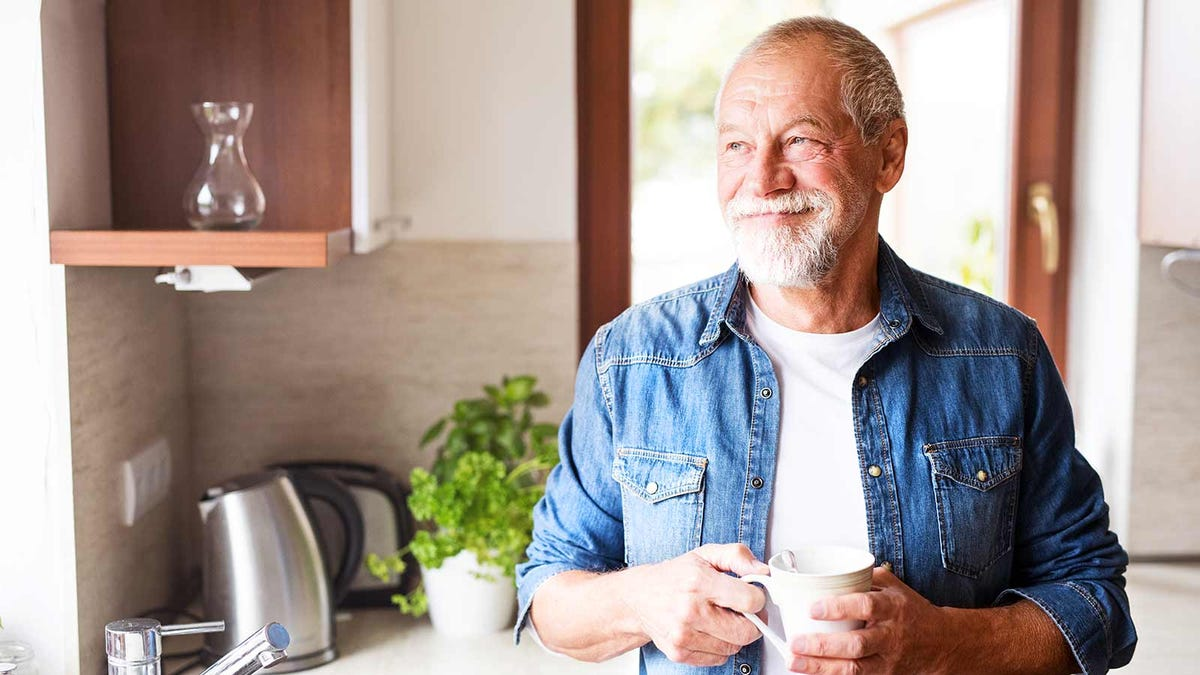An older man holding a coffee mug in a kitchen.