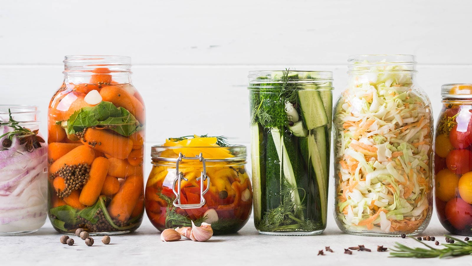Jars of pickled vegetables loaded with brine and spices.