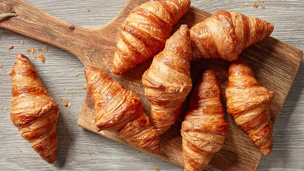 Freshly baked croissants on a cutting board.
