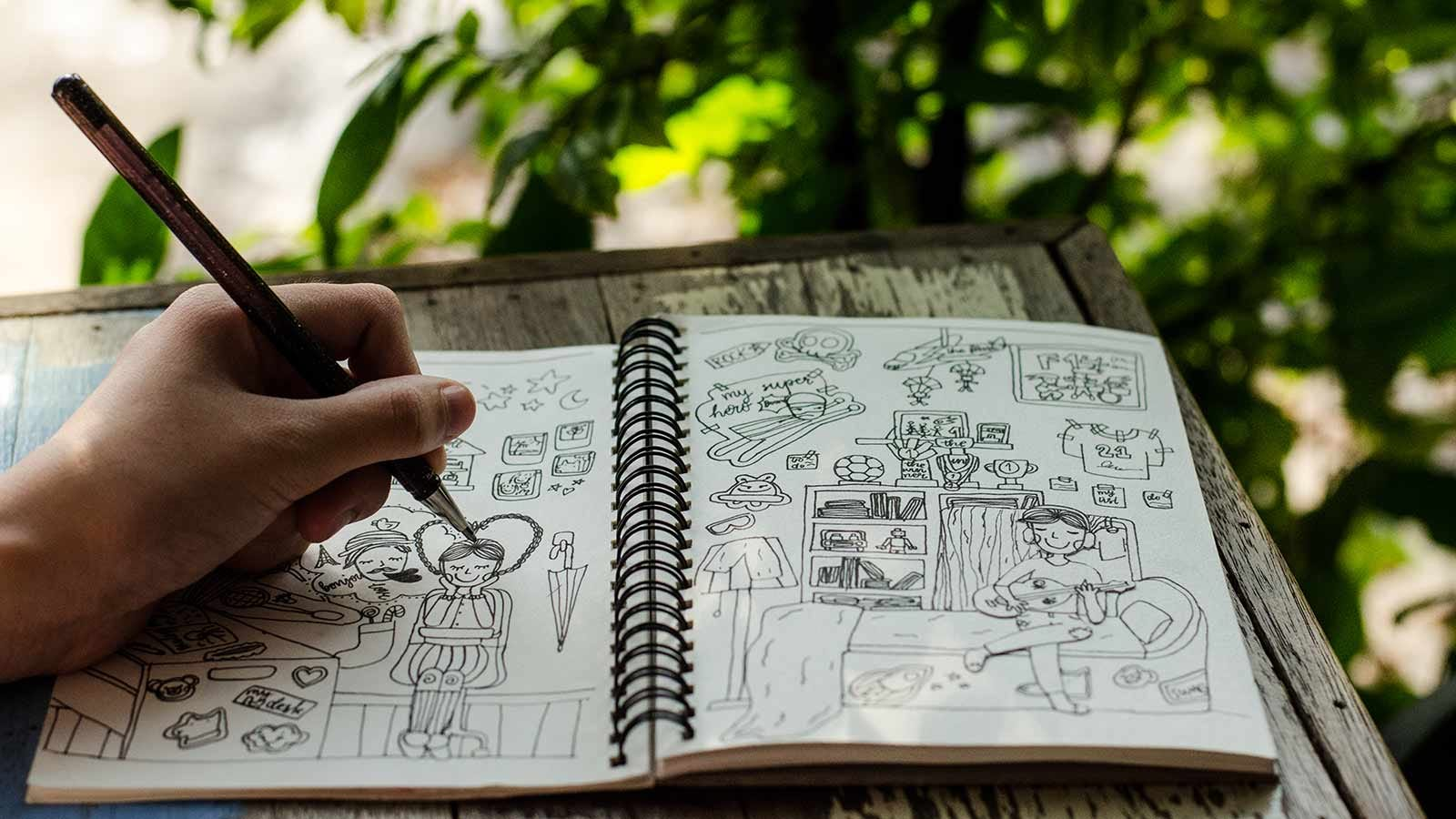 A hand drawing cartoons in a sketchbook.