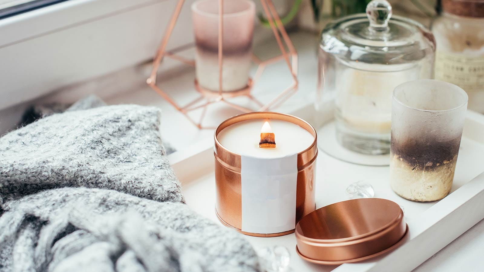 A candle on a tray beside a soft blanket and decorative items.