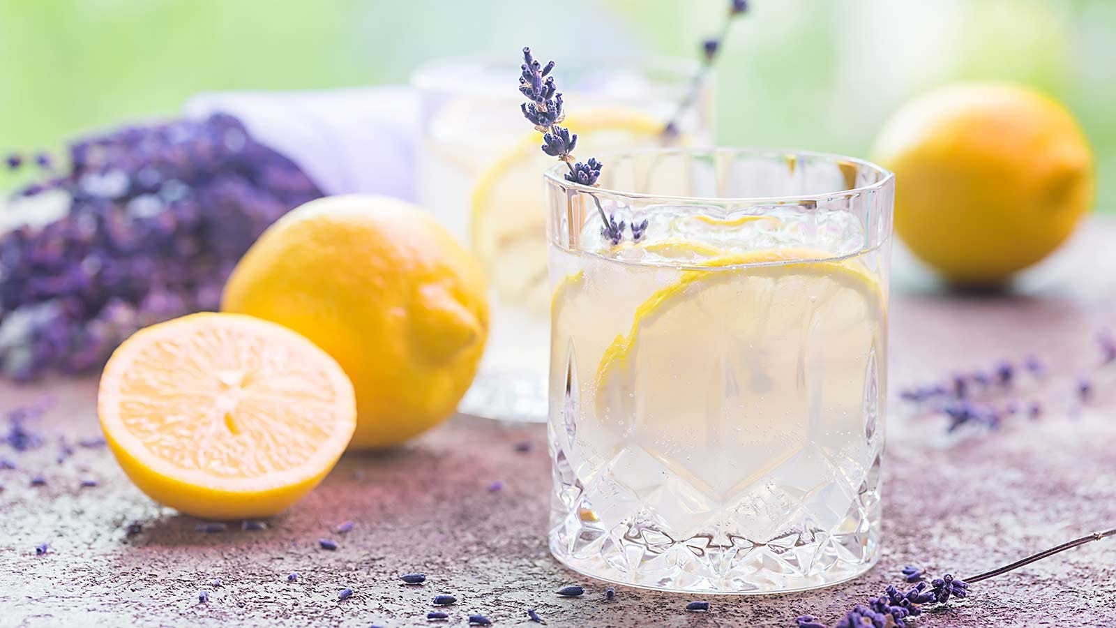 A glass of lavender-infused lemonade, surrounded by lemons and sprigs of lavender.