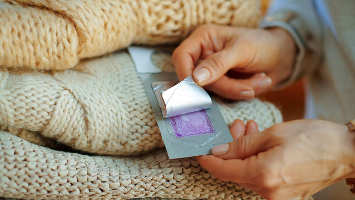 A woman opening a packet of lavender moth repellent and putting it in with her sweaters.