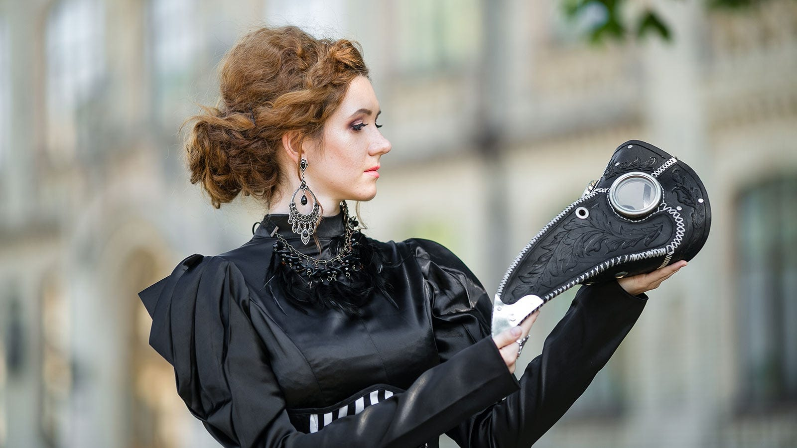 A red-haired woman in a black Victorian dress holding a plague doctor mask.