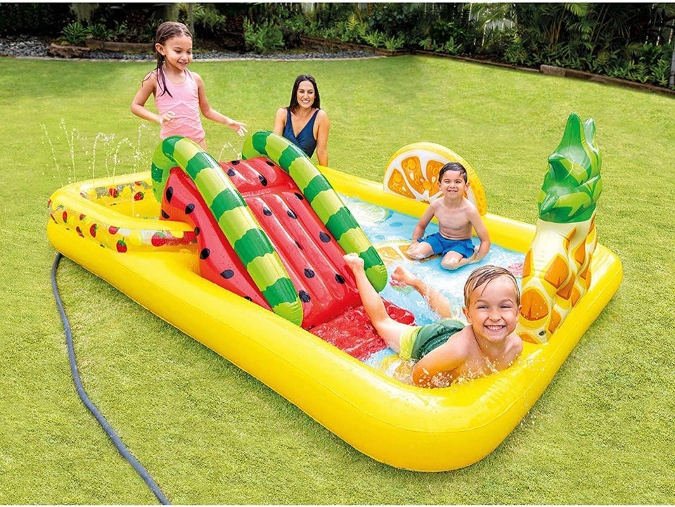 Children playing in a fruit themed wading pool with a watermelon slide, plus a woman supervising outside the pool.