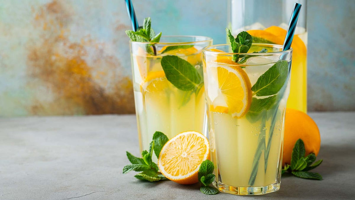 Two glasses of lemonade mojito cocktails with fresh-cut lemons and mint.