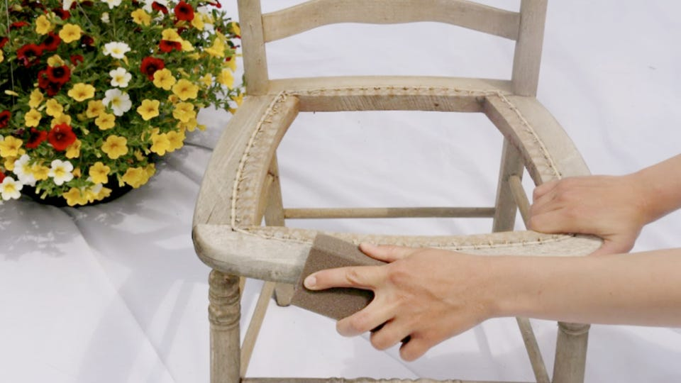 Someone sanding a chair with a sanding block.