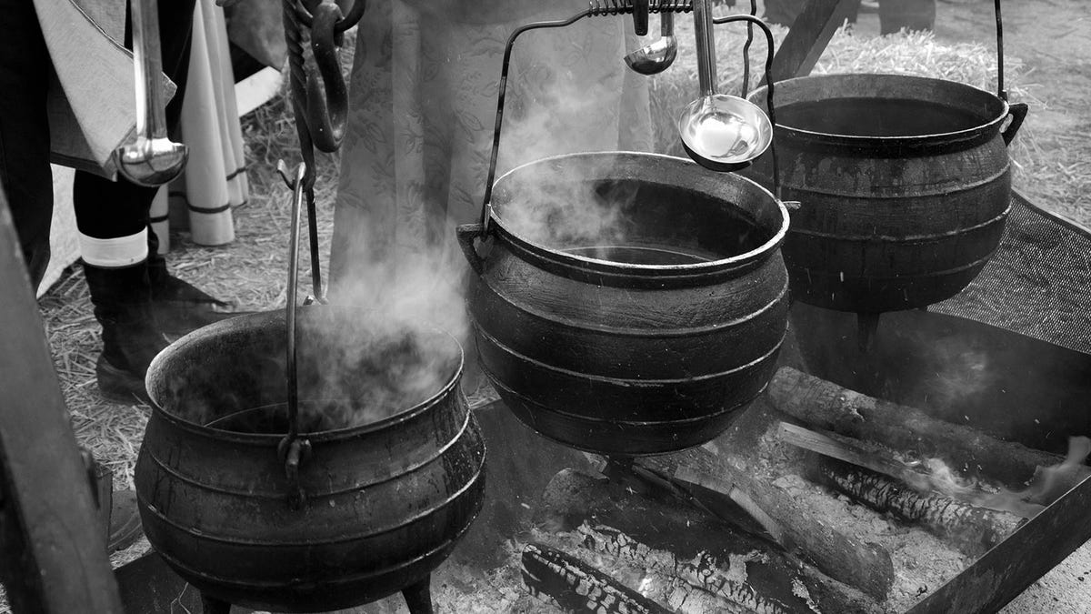 Stewpots boiling over a fire.