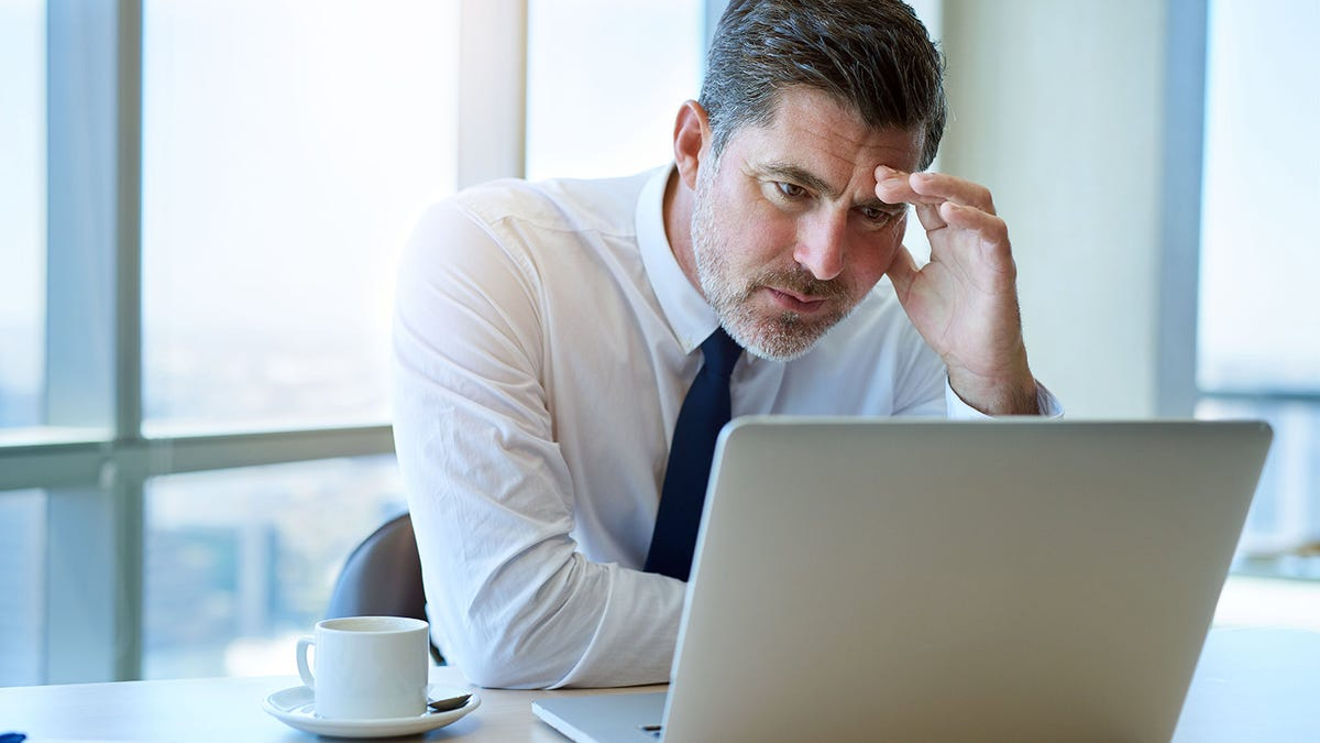 A man staring at a laptop in an office, reading work emails.