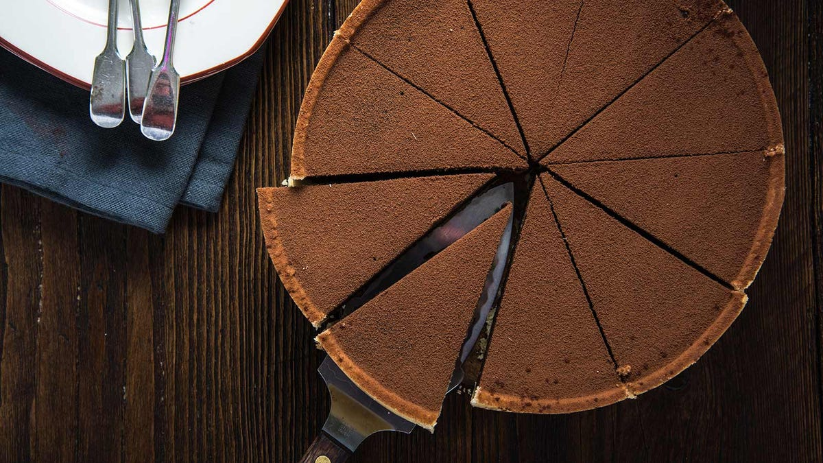 A chocolate cake, dusted with cocoa powder, cut into slices.