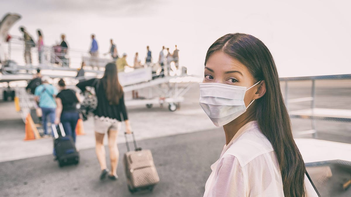 Woman boarding an airplane in China, wearing a face mask.