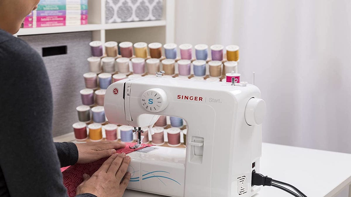 woman sitting at a sewing table and operating a white sewing machine on a piece of pink fabric