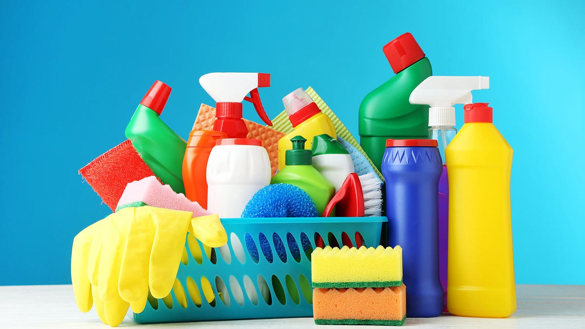 A variety of cleaning products and supplies in a plastic basket.