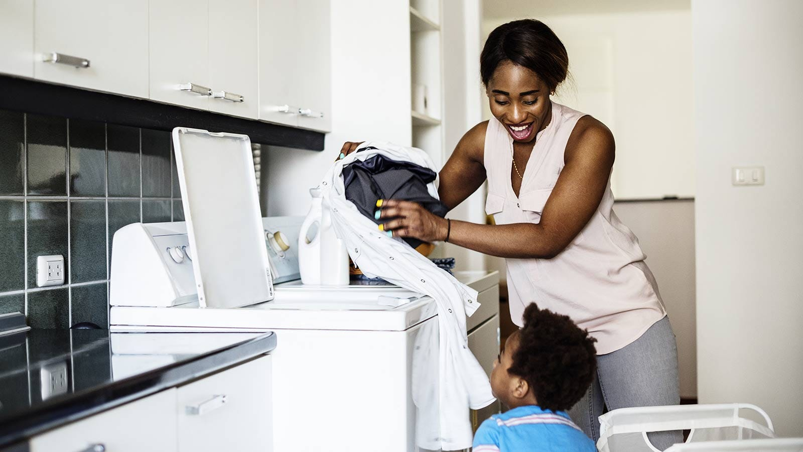 Woman loading clothing in the washing machine while talking to her child.