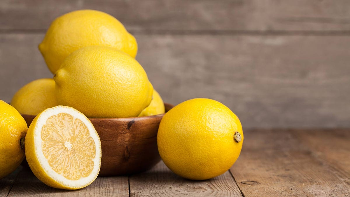 Lemons in a wooden bowl sitting on a rustic table.