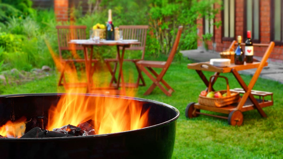 A backyard with a fire pit , outdoor furniture, and a beverage cart.