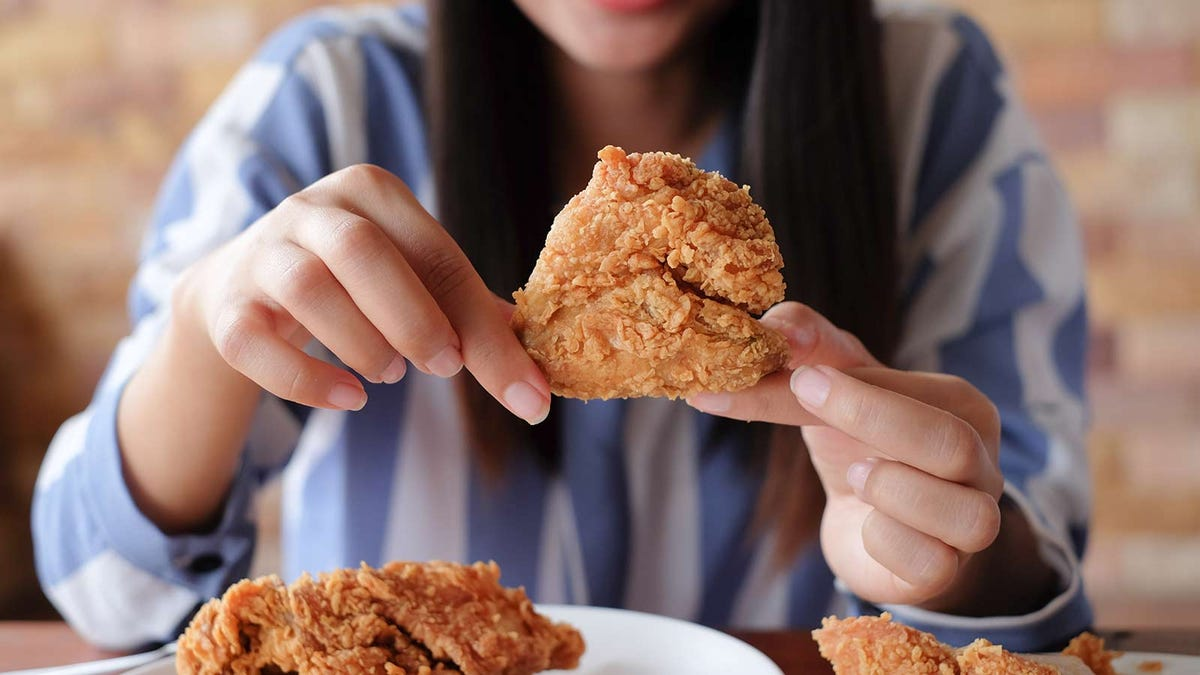 A woman holding homemade KFC-style fried chicken.