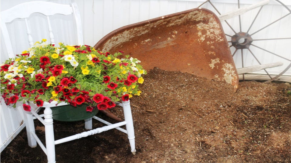 A chair planter filled with colorful flowers next to a rusted wheelbarrow and wagon wheel.