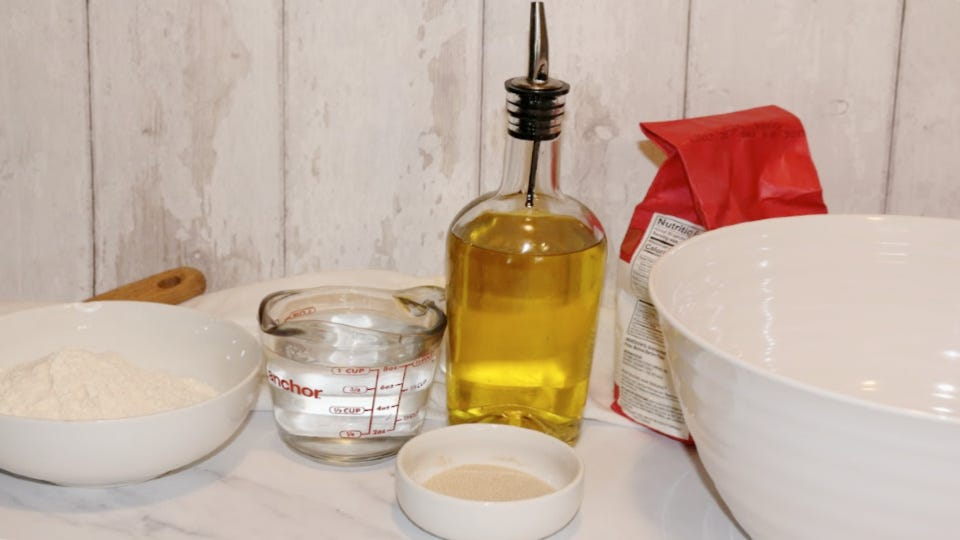 Ingredients for a focaccia bread dough, including olive oil, water, yeast, and flour.