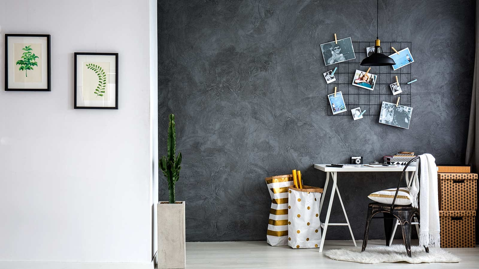 A home workspace with personal photos on a decorative grid hanging above a desk.