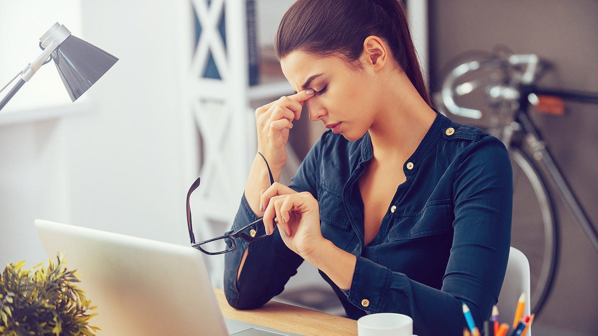 A woman holding her glasses and rubbing the bridge of her nose while sitting at a desk.