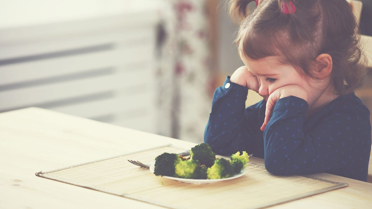 An unhappy toddler girl frowning, looking at broccoli on a plate.