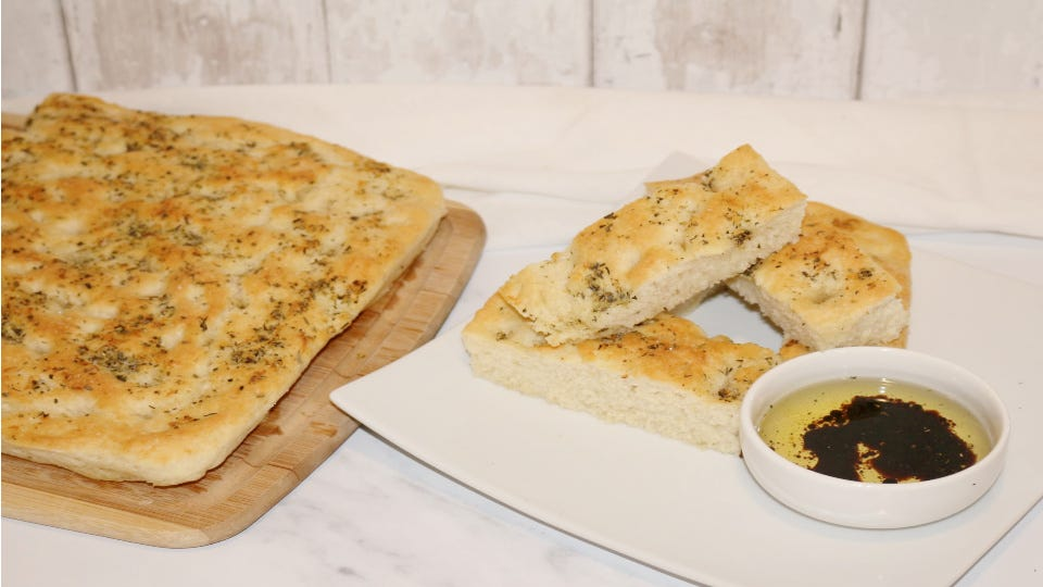 A freshly baked focaccia bread, cut into pieces and served with olive oil and balsamic vinegar.