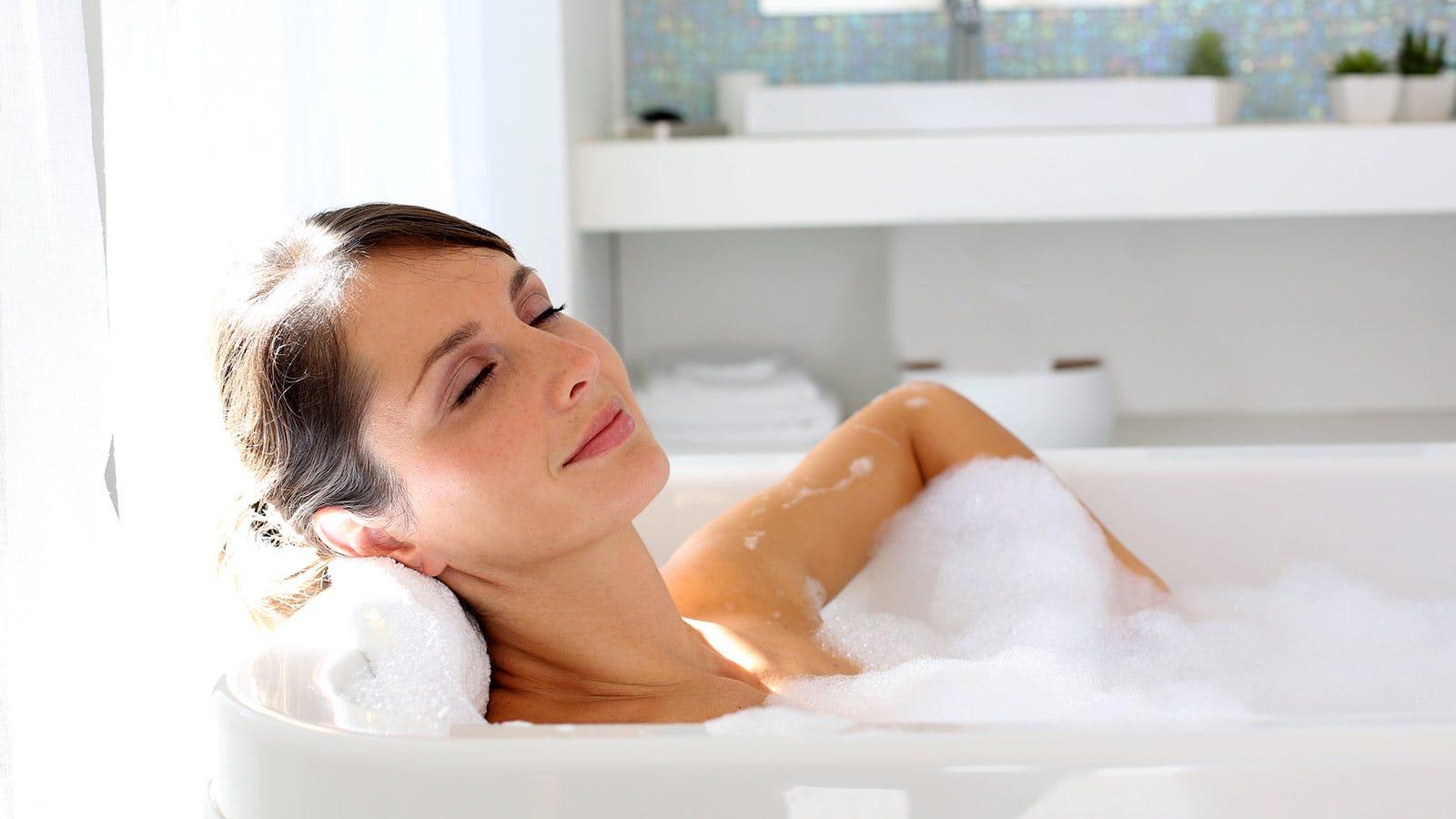 A woman relaxing in a bubble bath.