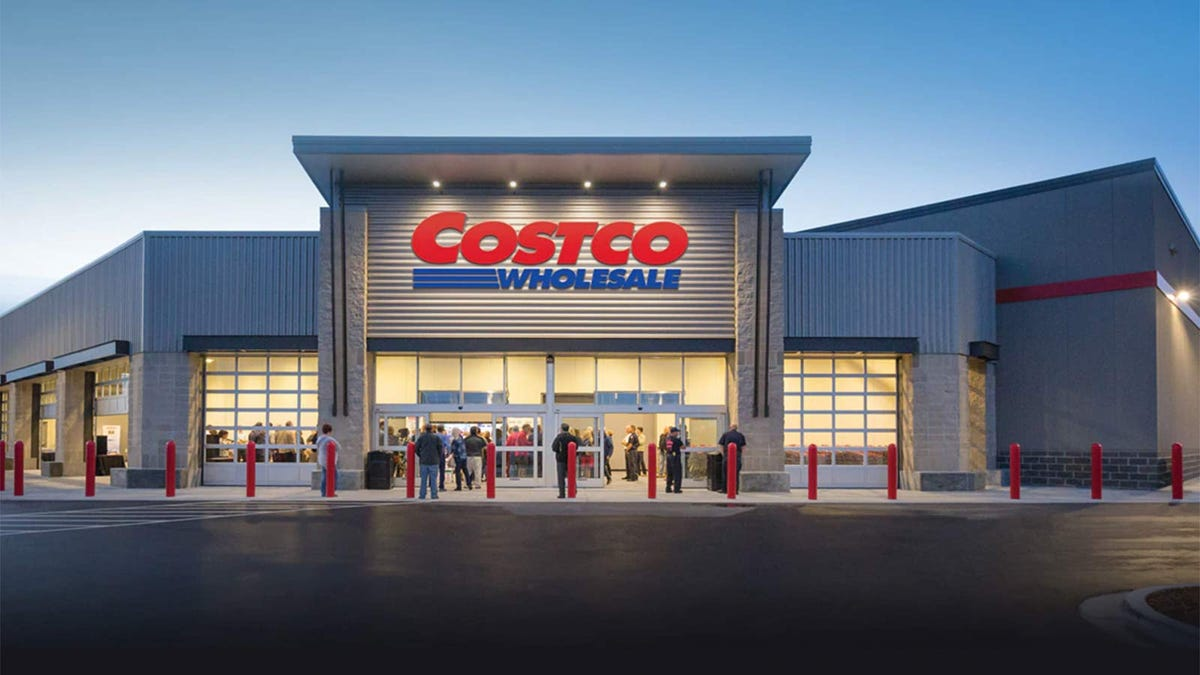 Exterior of a Costco store as shoppers stream in.