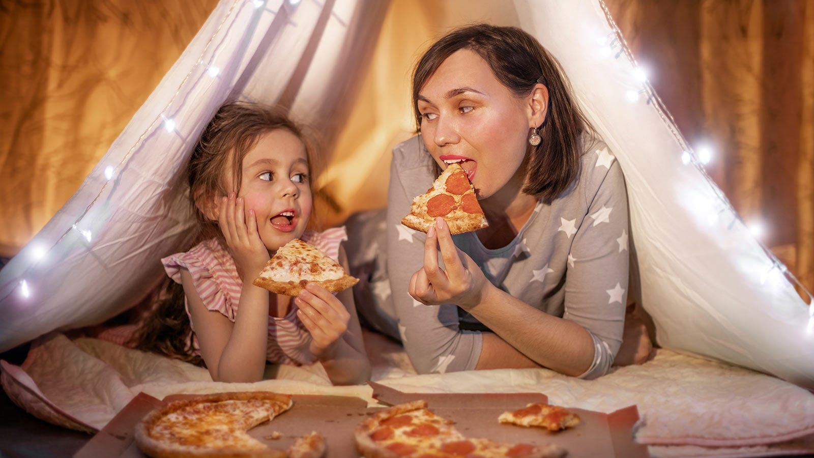 A mother and daughter having fun eating pizza in a tent set up in their living room.