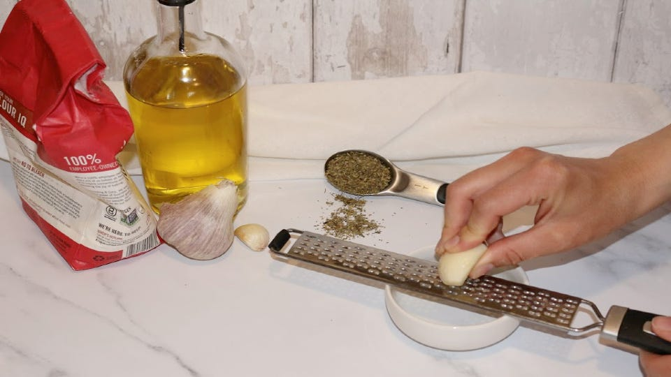 Using a microplane grater to grate garlic into a small pincher bowl, with oil, flour, garlic and Italian herbs in the background.