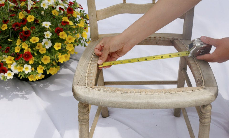 Someone measuring the center of a chair with the seat cut out with a tape measure.